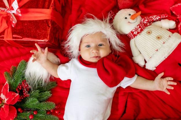 Un bambino divertente in un costume da babbo natale sdraiato su uno sfondo rosso tra i regali