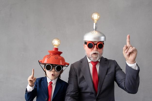 Bambino divertente e uomo anziano fingono di essere uomini d'affari. nonno e bambino che giocano in casa. istruzione, avvio e concetto di idea di business