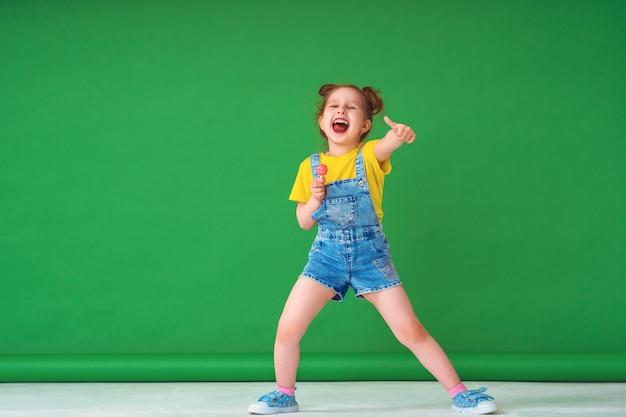 Il bambino divertente mostra il gesto di approvazione, con una lecca-lecca su un bastone fuori la lingua.