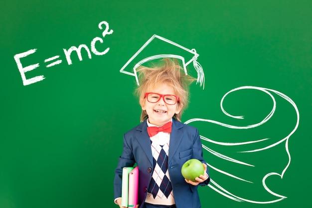 Studente bambino divertente in classe contro la lavagna verde.