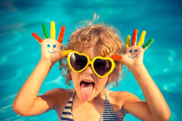 Bambino divertente con faccina di disegno sulle mani in piscina