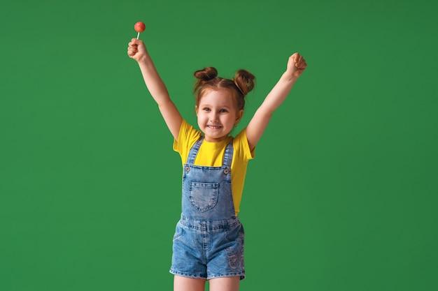Bambino divertente con le mani sollevate in aria. la ragazza con un lecca-lecca è divertente