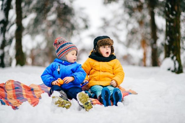 Bambini divertenti con volti espressivi fanno festa invernale nella foresta innevata