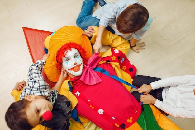 Pagliaccio divertente e bambini piccoli sdraiati sul pavimento e tirano le mani