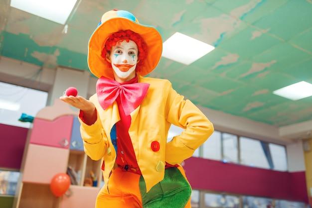 Il pagliaccio divertente posa con il naso rosso a disposizione. festa di compleanno che celebra nella stanza dei giochi, festa del bambino nel parco giochi