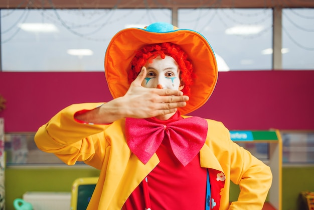 Il pagliaccio divertente mostra i trucchi con le espressioni facciali nell'area dei bambini. festa di compleanno in sala giochi, vacanza per bambini nel parco giochi. felicità dell'infanzia, svago infantile, intrattenimento con l'animatore