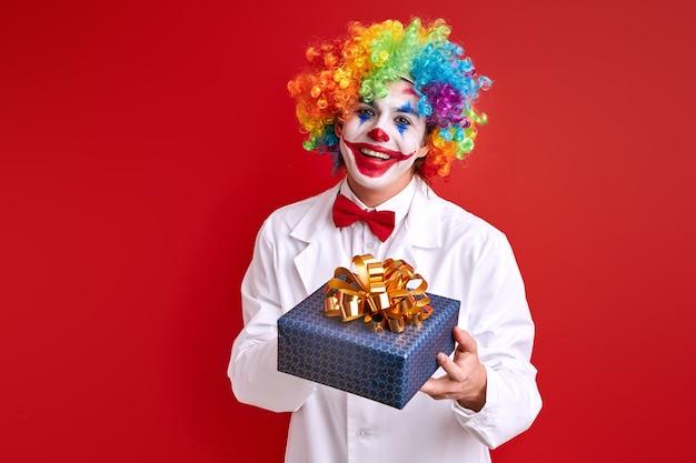 Pagliaccio divertente con una confezione regalo isolata su sfondo rosso, giovane arlecchino che guarda l'obbiettivo