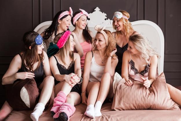 Divertenti giovani donne fresche indossano pigiami, le migliori amiche che si divertono insieme godono la festa della spa addio al nubilato in camera da letto