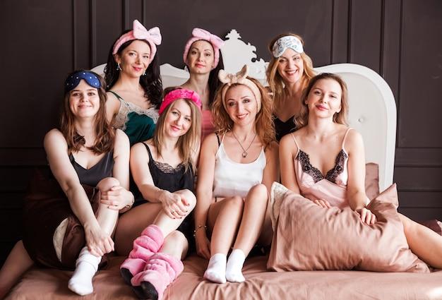 Divertenti giovani donne fresche indossano pigiami guardando la fotocamera, le migliori amiche che si divertono insieme godono la celebrazione della spa addio al nubilato in camera da letto