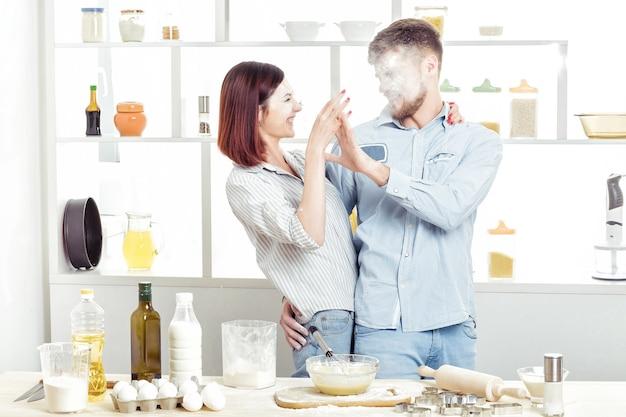 Coppia divertente in amore cucinare la pasta e divertirsi con la farina in cucina