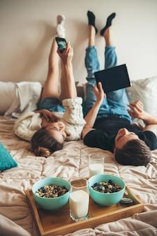 Coppia divertente sdraiata a letto prima di mangiare cereali con latte e utilizzo di telefono e tablet