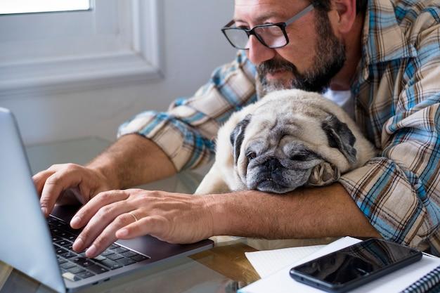 Cane e uomo divertente delle coppie lavorano insieme a casa con il computer di lavoro in linea del computer portatile nel concetto di amicizia e felicità dello stile di vita digitale del lavoro intelligente per le persone moderne