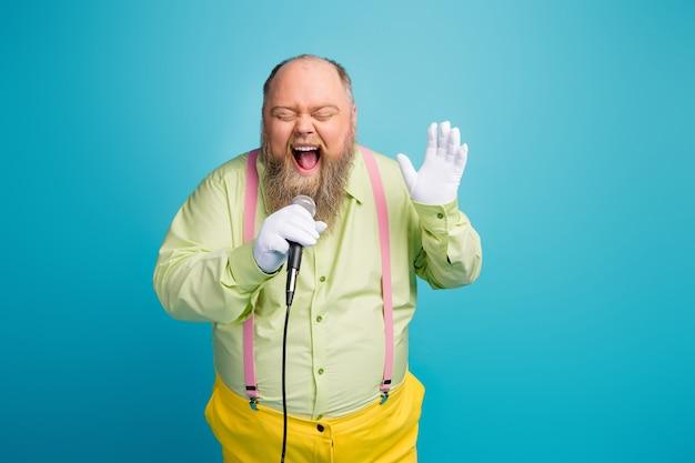 Uomo grasso pazzo divertente che canta nel microfono su priorità bassa blu