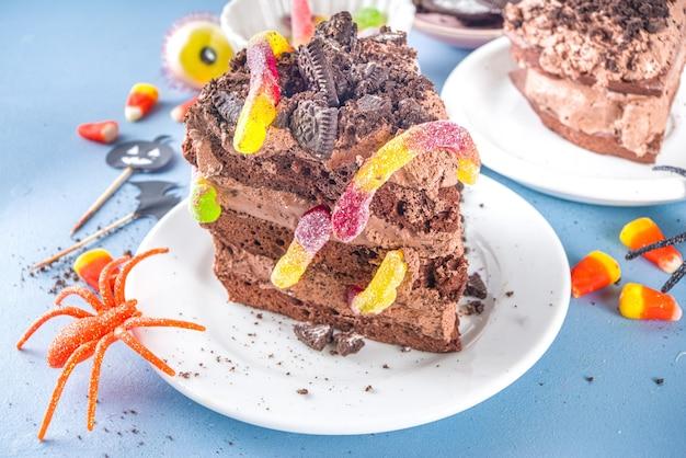 Torta divertente e raccapricciante per la festa dei bambini di halloween, idea dessert creativa, pezzo di torta al cioccolato con vermi di marmellata, dolci e caramelle tradizionali di halloween, spazio per le copie
