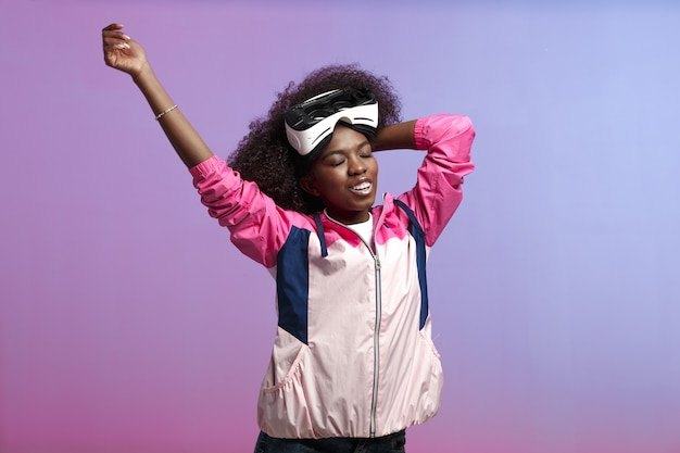 Divertente ragazza dai capelli castani riccia vestita con la giacca sportiva rosa indossa sulla testa gli occhiali per realtà virtuale in studio su sfondo al neon.