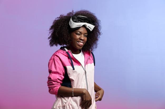 Divertente ragazza dai capelli castani riccia vestita con la giacca sportiva rosa indossa in testa gli occhiali per realtà virtuale in studio su sfondo al neon.