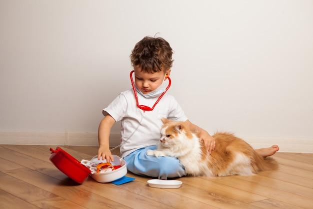 Il bambino riccio divertente in una mascherina medica e occhiali con uno stetoscopio sul collo gioca un medico con un gatto. il bambino vuole iniettare al gatto una siringa giocattolo.