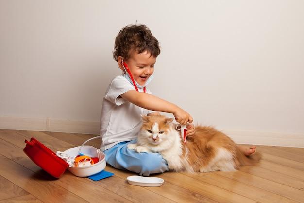 Il bambino riccio divertente in una mascherina medica e occhiali con uno stetoscopio sul collo gioca un medico con un gatto.