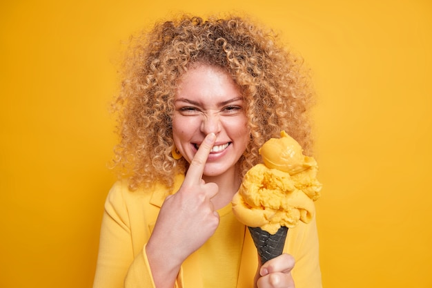 La donna riccia divertente con l'espressione positiva tocca il suo naso sorride felicemente sciocchi intorno tiene un gelato appetitoso vestito in abito formale isolato sul muro giallo. mi piacciono i dolci