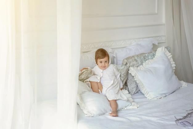 Piccola ragazza sorridente castana divertente e sveglia che gioca saltando sul letto in camera da letto leggera. interni bianchi con letto grande. infanzia, scuola materna, giovinezza, concetto di relax