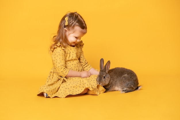 Ragazza sveglia divertente del bambino in vestito giallo con la seduta del coniglio.