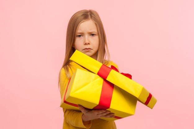 Bambino carino divertente infelice con il cattivo regalo di compleanno. ritratto di una bambina triste che apre una confezione regalo e guarda la telecamera con un'espressione insoddisfatta. studio al coperto isolato su sfondo rosa