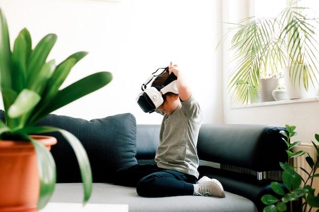 Ragazza carina divertente guardando qualcosa che viene visualizzato negli occhiali di realtà virtuale, seduto sul divano. concetto di tecnologia moderna