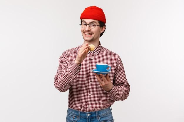 Collega maschio carino divertente che ha conversazione alla cucina dell'ufficio come bere il tè e mangiare il biscotto