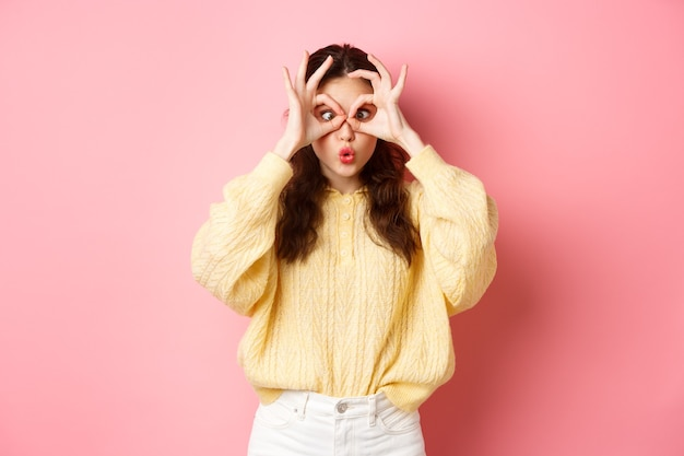 Divertente e carina giovane donna increspa le labbra facendo facce divertenti guardando attraverso il binocolo a mano e gli occhi socchiusi in piedi contro il muro rosa
