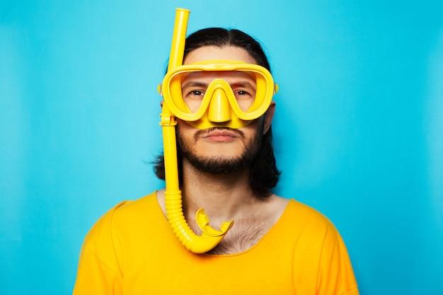 Divertente uomo subacqueo che indossa attrezzatura subacquea gialla su sfondo blu.
