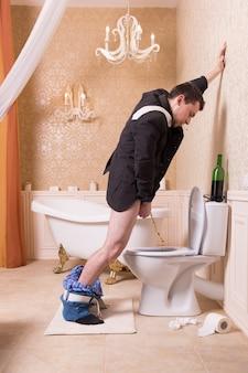 Urina divertente dell'uomo ubriaco nella tazza del gabinetto. interno del bagno in stile vantaggioso