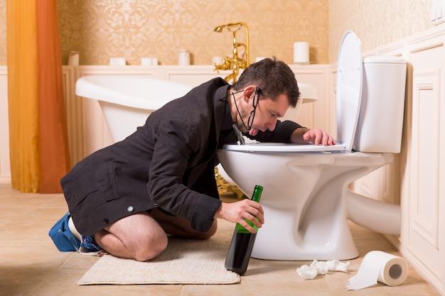 Uomo ubriaco divertente con una bottiglia di vino malato nella tazza del gabinetto. interno del bagno di lusso
