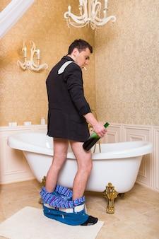Divertente uomo ubriaco con una sigaretta in bocca e una bottiglia di alcol in mano pipì nel bagno di lusso
