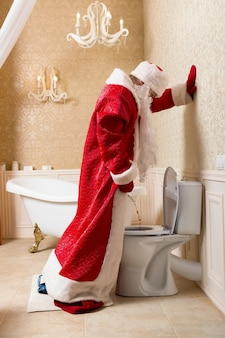 Divertente babbo natale ubriaco in costume rosso pipì nella toilette. babbo natale alcolizzato