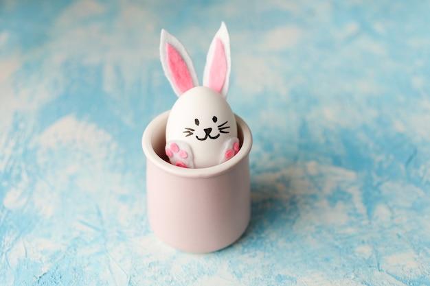 Coniglietto di pasqua divertente posto nella tazza rosa su sfondo blu.