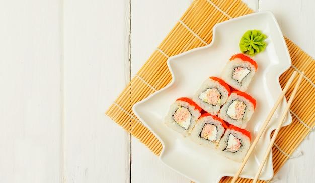 Divertente albero di natale commestibile a base di sushi, idea creativa per ristorante giapponese sul tavolo bianco. . vacanza, celebrazione, concetto di arte del cibo. copyspace.