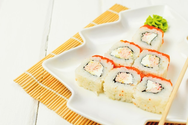 Divertente albero di natale commestibile a base di sushi, idea creativa per ristorante giapponese sul tavolo bianco. . vacanza, celebrazione, concetto di arte del cibo.