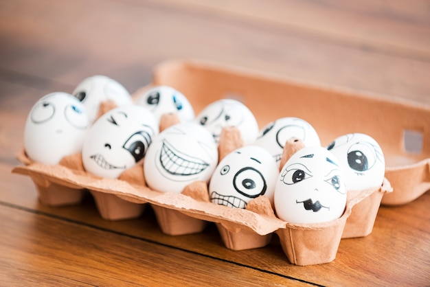 Uova divertenti. primo piano di uova divertenti con diverse emozioni che giacciono in un contenitore sulla scrivania di legno