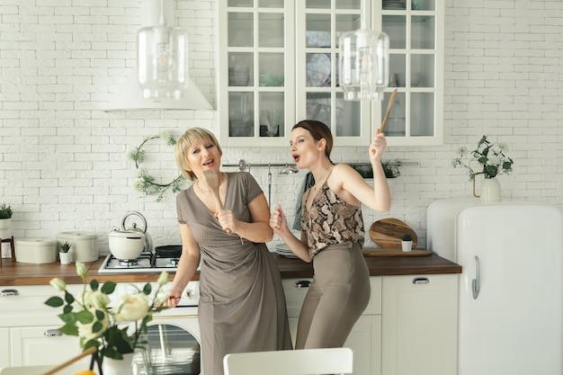 Divertente madre anziana divertendosi in cucina con una figlia adulta