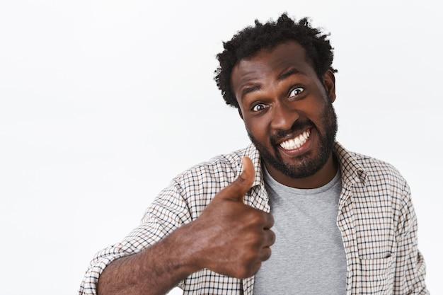 Un ragazzo afroamericano felice, divertente ed entusiasta alza il pollice ottimista, sorride soddisfatto, concorda con la scelta di qualcuno