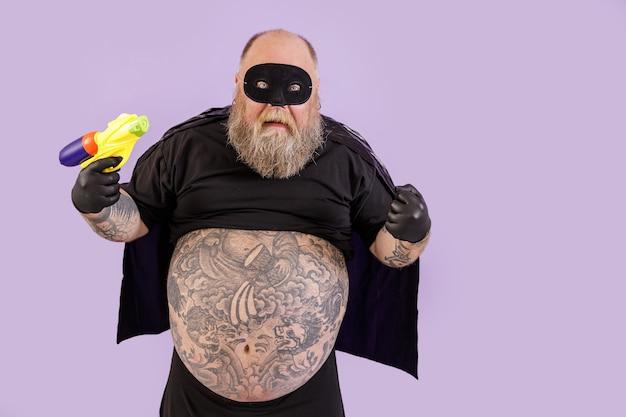 L'uomo obeso diabolico divertente in costume di carnevale tiene il blaster del giocattolo che posa sul fondo porpora