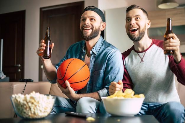 Divertenti amici barbuti hipster eccitati con snack e birre guardando la pallacanestro in tv mentre era seduto sul divano a casa e i fan gridavano
