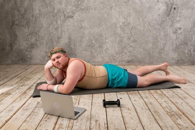 Divertente uomo grasso facendo sport sul materassino yoga, facendo sport online, esaminando il laptop.