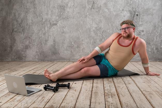 Divertente uomo grasso che fa sport sul materassino yoga, fare sport online