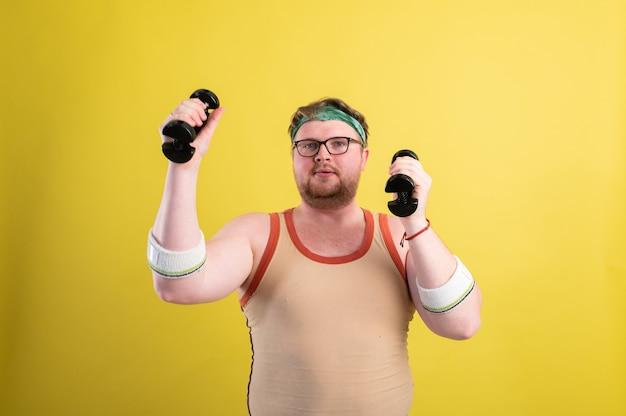 Uomo grasso divertente in abiti sportivi con manubri nelle sue mani. l'uomo in sovrappeso fa sport. sfondo giallo isolare.