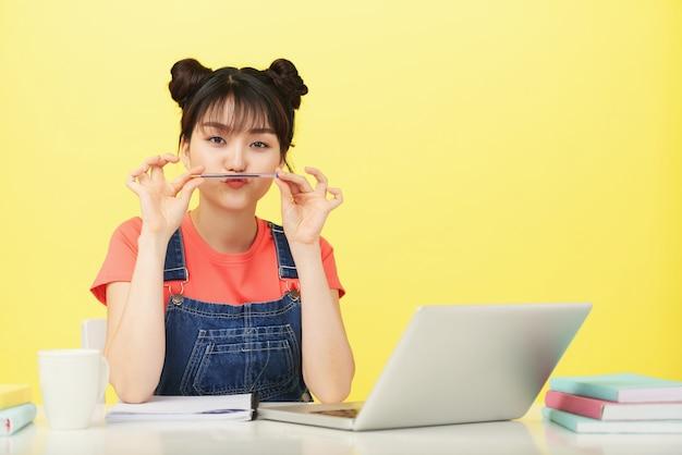 Divertente studentessa universitaria che fa i baffi con la penna quando è seduta alla sua scrivania