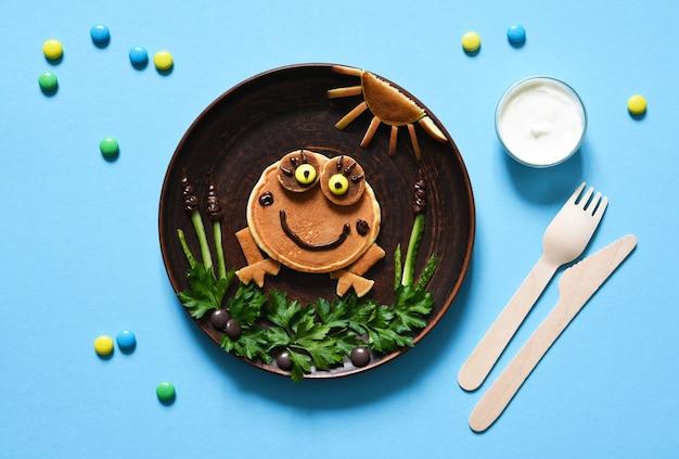 Rana divertente fatta di frittelle su un piatto, vista dall'alto. colazione per bambini.