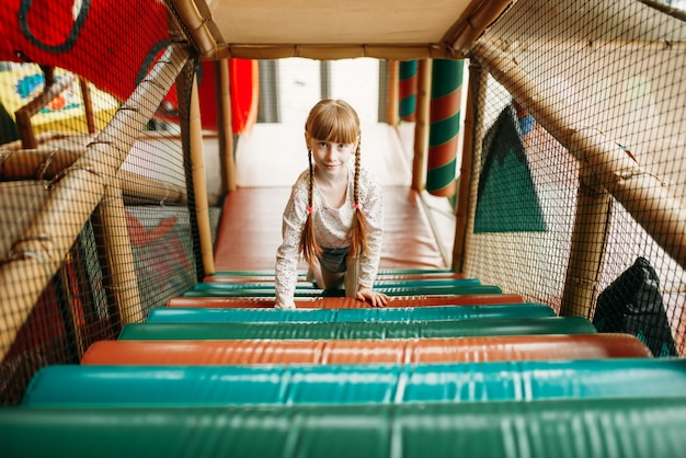 Ragazza divertente nella zona di arrampicata, centro giochi per bambini