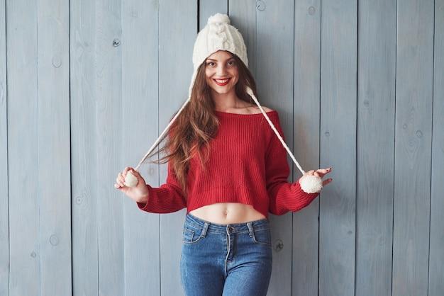 Ragazza divertente in maglione lavorato a maglia e cappello in piedi al chiuso con parete in legno.
