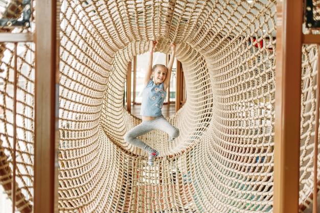 Ragazza divertente gioca in rete di corda, centro giochi per bambini